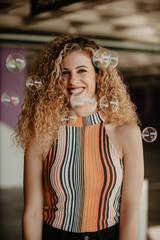 Playful stylish woman and soap bubbles