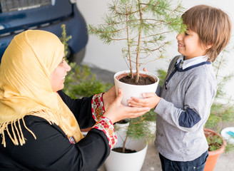 Parent potting and planting with kid