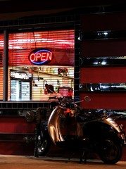MOPED PARKED OUTSIDE DINER WITH NEON LIGHTS AT NIGHT