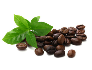 scattered roasted coffee beans and leaves on white  background