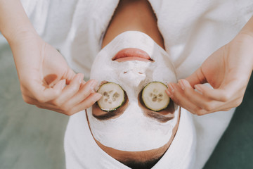 Woman Lie with Cosmetic Mask with Cucumbers in Eyes.