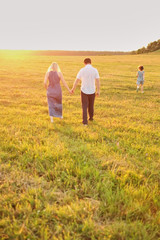 happy family husband wife and daughter run away into the sunset field