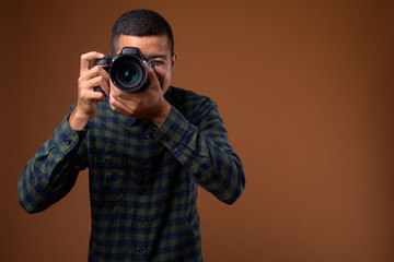 Young multi-ethnic Asian man against brown background