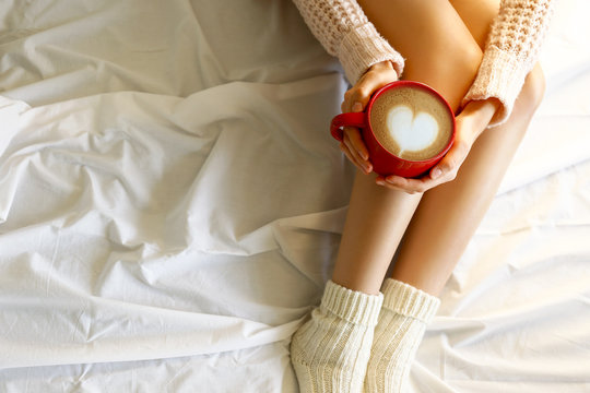 Young woman drinking cappuccino coffee and sitting in bed with white linnen. Top view of female legs in warm wool socks & sweater. Comfort winter holidays concept. Close up, copy space, background.