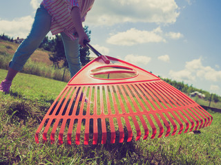 Unusual angle of woman raking leaves