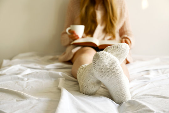 Lazy afternoon concept. Close up shot of woman sitting in bed leaning on the white wall in morning light, by the window reading old book, having cup of cappuccino coffee. Background, copy space