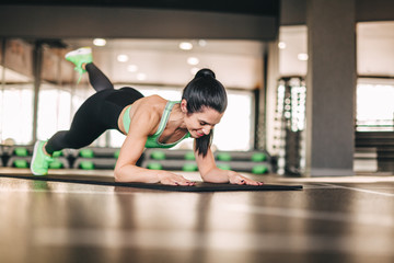 Athletic woman doing exercise on mat
