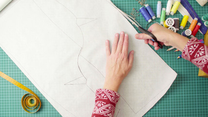 Top view. Middle-age woman hands with scissors cutting paper template. Handmade clothes.