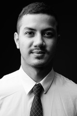 Young multi-ethnic Asian businessman against gray background in