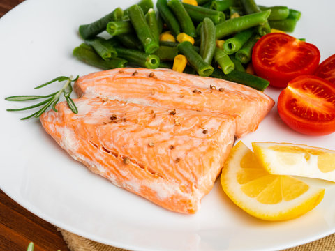 Fish salmon steamed with vegetables. Healthy diet food, dark wooden backdrop, side view, close-up