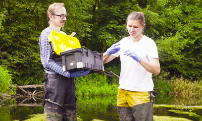 Man and woman scientist environmentalist standing in a river. Woman taking sample of water. Man holding toolbox