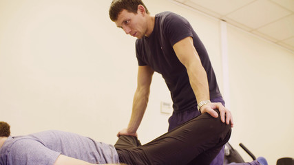 Doctor physiotherapist doing stretching exercises for young disable man at the rehabilitation clinic