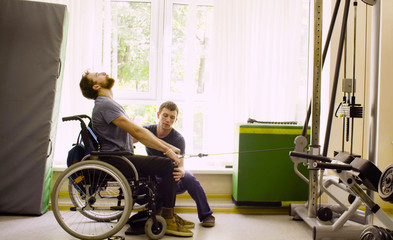 Young disabled man in wheelchair doing strength exercises for hands in the rehabilitation clinic. Doctor physiotherapist helping him