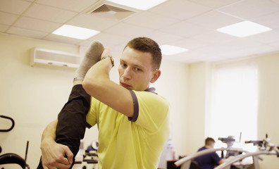 Close up face of doctor physiotherapist helping disabled man, doing leg exercises at the rehabilitation center. Health reductive gymnastics.