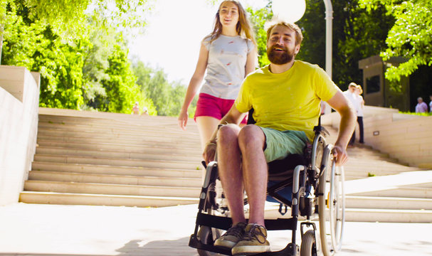 Young disable man in a wheelchair on a walk in the park with his wife.