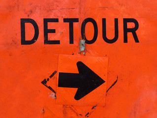 Battered orange DETOUR sign with arrow.