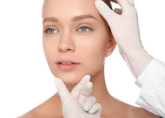 Doctor examining young woman face before cosmetic surgery on white background