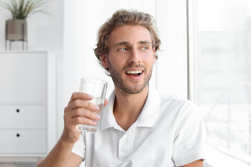 Young man holding glass of clean water indoors