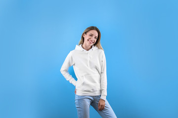 Wall Mural - Portrait of woman in hoodie sweater on color background. Space for design