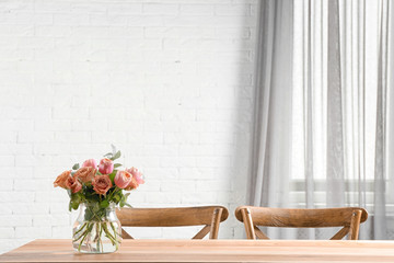 Vase with beautiful flowers as element of interior design on table in room. Space for text