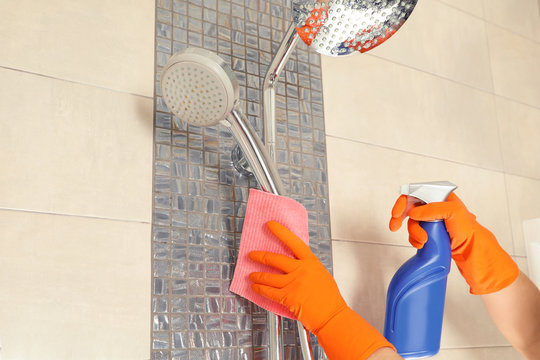 Woman in protective gloves cleaning shower with rag, closeup