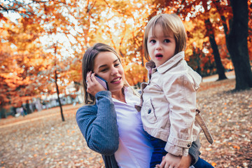 Mother and daughter in the park enjoying the beautiful autumn nature.