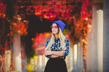 Young white style girl in red glasses and shirt in a red grapes alley. Autumn season