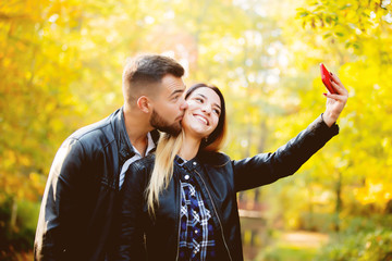 Young white couple make a selfie on mobile phone in a park with yellow trees on background. Autumn season time