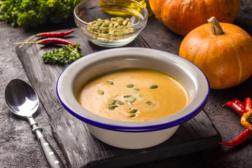 Seasonal autumn food - Spicy pumpkin soup with cream and pumpkin seeds.