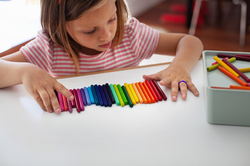 A child lines up colorful crayons in a row.
