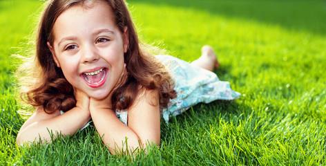 Foto auf AluDibond Artist KB Cute little girl resting on a warm, fresh green lawn