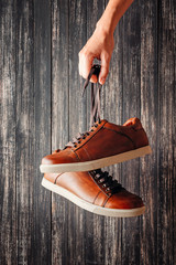Hand holds for laces brown leather men's shoes on a dark background