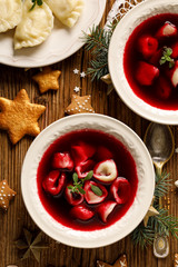 Wall Murals Ready meals Christmas beetroot soup, borscht with small dumplings with mushroom filling in a ceramic bowl on a wooden table, top view. Traditional Christmas eve dish in Poland.