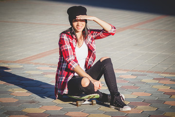 Beautiful woman with a skateboard on the street