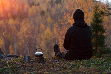 A tourist makes tea at sunset in the autumn forest. To the left is a kettle on the alcohol stove and a titanium mug.