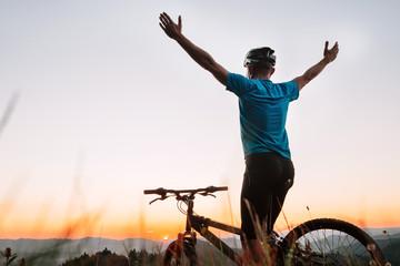 Man biker greats a sunset in mountains