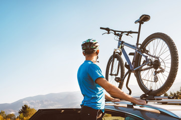 Man take his bicycle from car roof