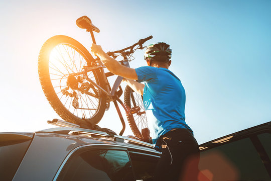 Mountain biker man take of his bike fron the car roof