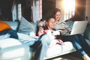 Lovely young couple at home. Happy man and woman sitting on the couch together and watching TV series on laptop. Bright loft apartment