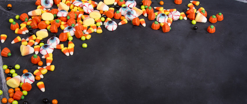 Halloween candy scattered over a black chalkboard
