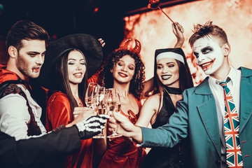 Young People in Halloween Costumes Clinking Glasses