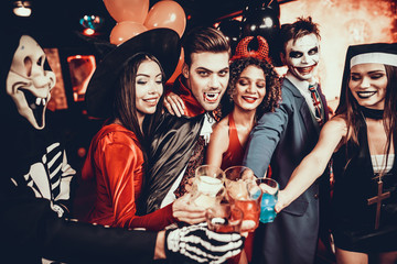Friends in Halloween Costumes Drinking Cocktails