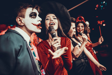 Wall Mural - Young People in Halloween Costumes Singing Karaoke