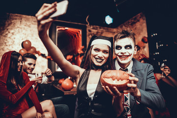 Wall Mural - Young Couple in Halloween Costumes taking Selfie