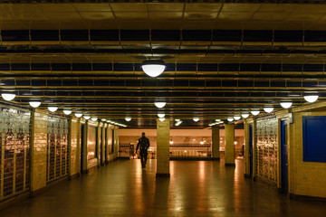 Interior view of man walk through tunnel passenger at Klosterstrasse underground train station in Berlin, Germany. Silhouette scenery of people  inside U-Bahn station with vintage yellow atmosphere.
