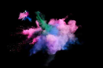 Bizarre forms of powder paint and flour combined  together explode in front of a black background to give off fantastic  multi colored cloud forms.