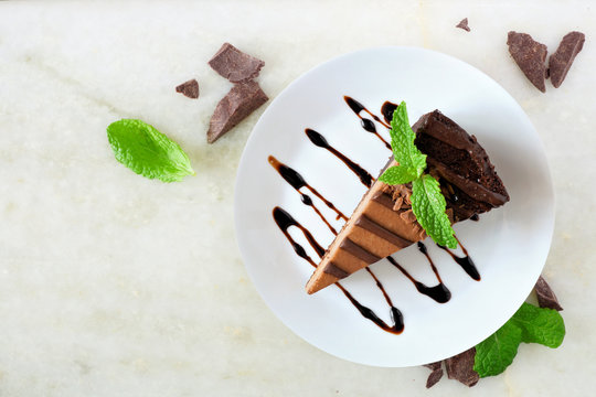 Slice of chocolate cheesecake on plate, above view over a white stone background