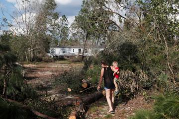 Lee Schaffrick, 45, carries her grandson, Mason Gray, 3, through debris from Hurricane Michael on her driveway in Fountain