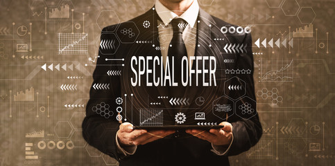 Special offer with businessman holding a tablet computer on a dark vintage background