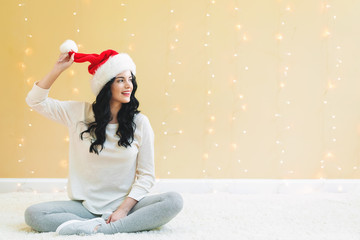 Happy woman with a Santa hat on a shiny light background